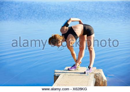 Runner Frau Stretching in einem See pier Outdoor. - Stockfoto