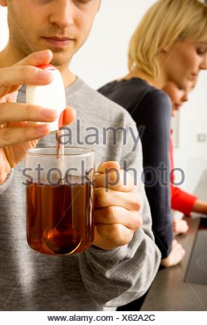 Junger Mann hält eine Tasse Kräutertee - Stockfoto