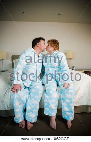 Paar in passenden Pyjamas küssen - Stockfoto