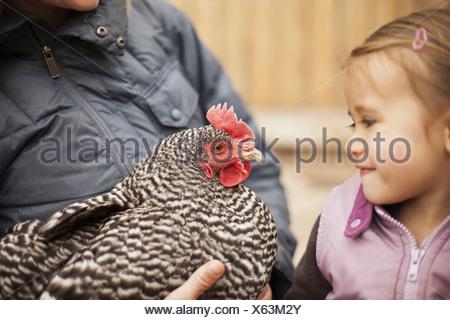 Eine Frau hält ein schwarz-weiß Huhn mit einem roten Coxcomb A jungen Mädchen neben ihr Betrieb eng an das Huhn - Stockfoto