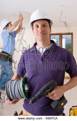 Elektriker mit Bohrer und Kabel Spule mit Kollege Verdrahtung Decke ...