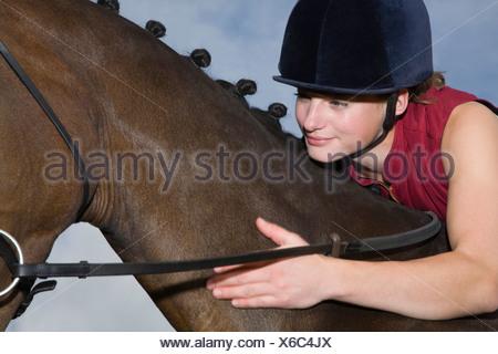 Mädchen umarmt Pferd, close-up - Stockfoto