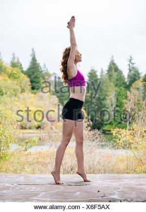 Seitenansicht der jungen Frau praktizieren Yoga im Wald am See - Stockfoto