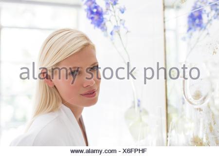 Frau stehend am Badezimmerspiegel - Stockfoto
