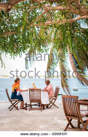 LAMU, KENIA, AFRIKA. Ein Mann Und Eine Frau Sitzen Unter Schatten  Spendenden Bäumen