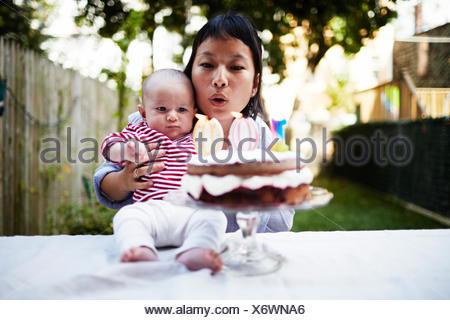 Mutter Baby Sohn halten, Ausblasen der Kerzen auf Kuchen - Stockfoto