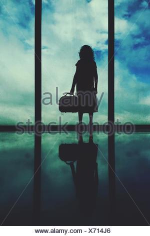 Silhouette eines Mädchens stehen am Flughafen Fenster - Stockfoto