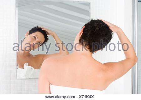 Frau im Spiegel betrachtet