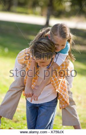 Junge Mädchen im Park Huckepack Fahrt geben - Stockfoto