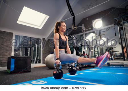 Junge Frau, training, dabei Sit up Push-Ups auf Wasserkocher Glocken im Fitness-Studio - Stockfoto