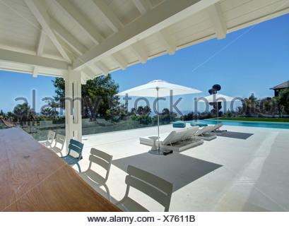 Weiße Liegestühle Am Pflaster Neben Türkisfarbenen Pool Vor