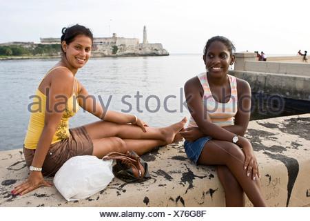 kubanische frauen sitzen auf einer mauer vor castillo de morro morro castle havanna kuba. Black Bedroom Furniture Sets. Home Design Ideas