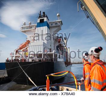 Arbeitnehmer auf Schlepper Boot mit Blick auf Schiff - Stockfoto