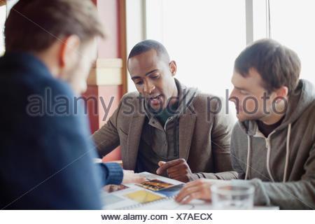 männlichen Freunden im Gespräch beim Mittagessen - Stockfoto