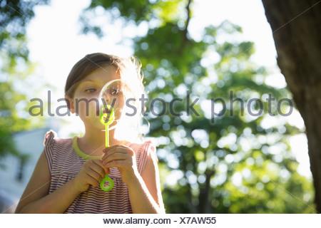 Im Freien im Sommer. Ein junges Mädchen bläst Seifenblasen in der Luft unter den Ästen eines großen Baumes. - Stockfoto