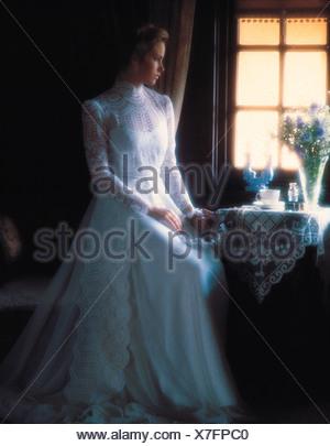Junge Frau in langen weißen Brautkleid Fenster sitzen. Stockfoto