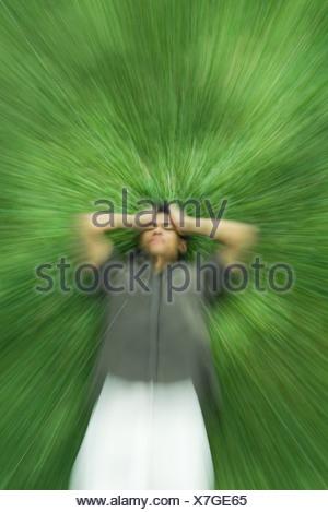 Mann auf Rücken Gras liegend mit geschlossenen Augen, Kopf, verschwommen Bewegung - Stockfoto