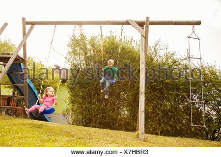 Bruder und Schwester spielen auf Schaukeln im Garten - Stockfoto