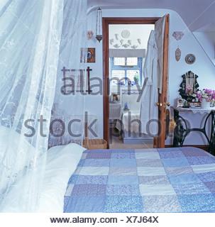 ... Weißen Voile Vorhänge Und Blauen Patchwork Quilt Auf Bett Im  Dachgeschoss Schlafzimmer Mit Tür Offen Für
