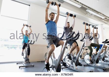 Spin-Klasse hält Hanteln overhead Heimtrainer Fitness-Studio - Stockfoto