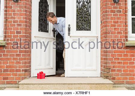 Mitte erwachsenen Mann mit Gabe vor Haustüre - Stockfoto