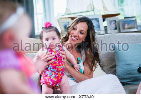 Junge Mutter mit Babymädchen im Wohnzimmer Stockfoto