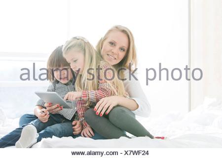 Porträt der glückliche Mutter mit Kindern bei der Nutzung digitalen Tablets im Schlafzimmer Stockfoto