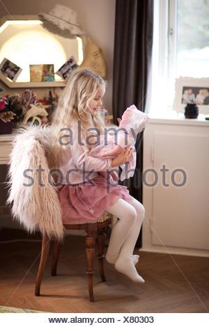 Mädchen spielen mit seiner Babypuppe. Tagespflege, Kind, Spielzimmer, behaupten Spiel.