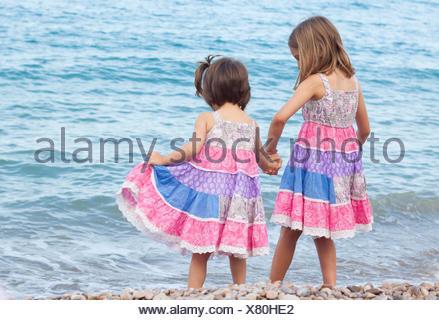 Zwei Schwestern stehen am Strand Hand in Hand - Stockfoto