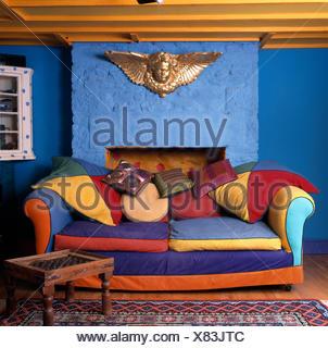 ... Ferienhaus Wohnzimmer; Gold Cherub Auf Wand über Eine Lebendige, Multi  Farbige Sofa In Einer Hellen Blauen Neunziger