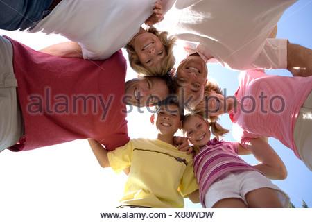 Drei Generationen Familie stehen im Huddle lächelnd nach oben im Hochformat - Stockfoto