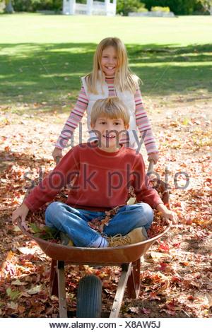 Mädchen 7 9 schieben Bruder 7 9 in Schubkarre im Garten Junge sitzt auf Herbst verlässt lächelnd Porträt - Stockfoto