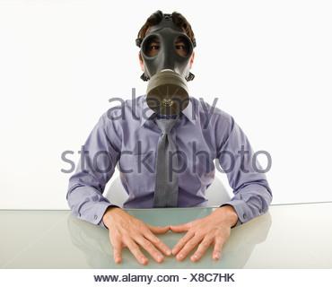 Geschäftsmann, sitzen in weißen Raum mit Gasmaske Stockfoto
