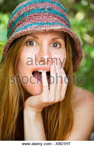 Porträt der hübsche rothaarige mit überrascht Ausdruck auf ihrem Gesicht trägt Hut - Stockfoto