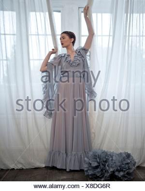 Eine Frau trägt eine langen graue Kleid, steht man vor einem Fenster Stockfoto
