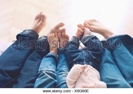 Ausgestreckten Beinen und barfuss Familie mit zwei Kindern - Stockfoto