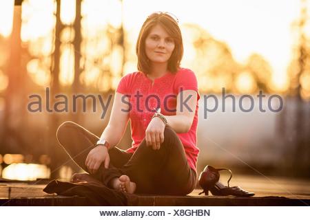 Frau sitzt im Schneidersitz auf Steinmauer