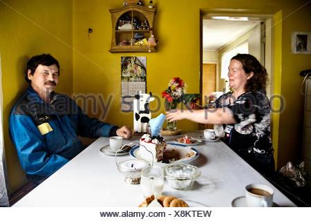 Ein paar mit Kaffee und Kuchen in ihrer Küche, Finnland. - Stockfoto