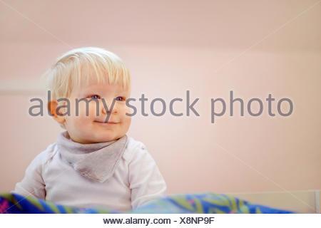 Porträt von niedlichen vierzehn Monate altes Baby Junge sitzt auf Bettdecke - Stockfoto