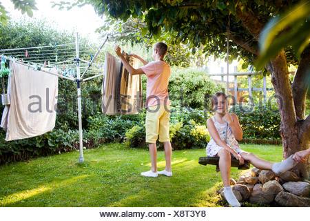 Porträt von Mädchen auf Schaukel mit Bruder Wäsche Arbeit im Hintergrund im Garten - Stockfoto