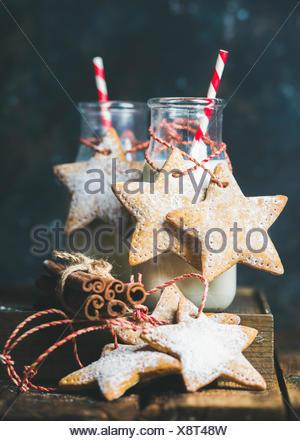 Flasche mit Milch für den Weihnachtsmann, Weihnachten festlich Lebkuchen sternförmige Cookies mit Dekoration Seil, Gewürze auf rustikalen Holztisch, dunkle Blau Zeitmessung - Stockfoto