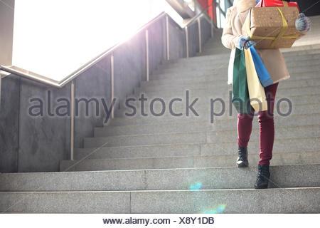 Niedrigen Winkel Blick auf Frau mit Geschenken und Einkaufstaschen Treppen hinunter bewegen - Stockfoto