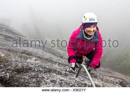 Klettersteigset Frauen : Eine frauen hat für die metall rung beim klettern klettersteig in