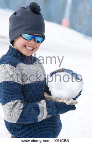 Jungen tragen wollene Mütze und Sonnenbrille, stehend im Schnee Feld Holding Schneeball, Lächeln, Porträt - Stockfoto