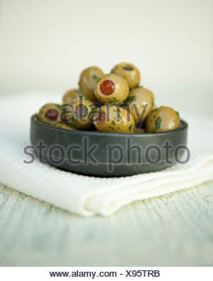 Grüne Oliven gefüllt mit Paprika mit Olivenöl und Kräutern in einem Topf