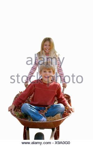 Porträt von Mädchen drängen junge in Schubkarren, Ausschneiden - Stockfoto