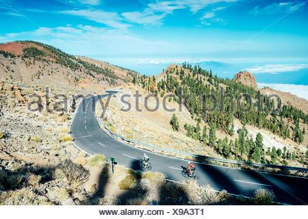 Zwei Radfahrer radeln auf Mountain Road, Nationalpark Teide, Teneriffa, Kanarische Inseln, Spanien - Stockfoto