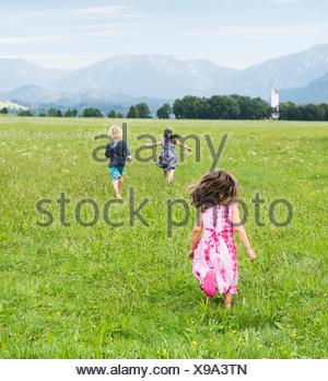 Rückansicht des Kinder laufen im Feld, Füssen, Bayern, Deutschland - Stockfoto