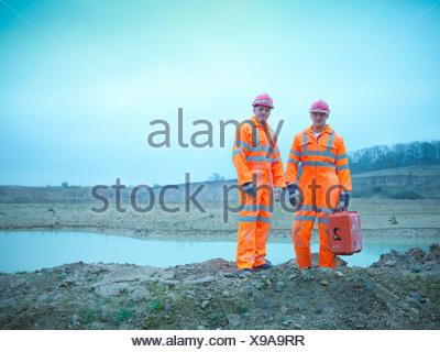 Arbeiter im Steinbruch Felsen stehend - Stockfoto