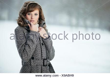 Porträt einer jungen Frau im Schnee, ihre Hand, die ihr Fell Kragen Stockfoto